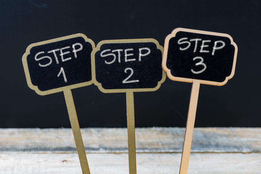 Business message Step 1, Step 2, Step 3 written with chalk on wooden mini blackboard labels, defocused chalkboard and wood table in background