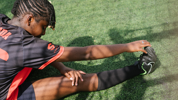 Teenager girl stretching before football