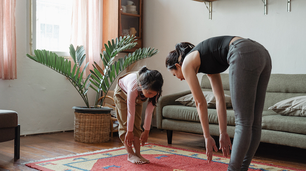 Asian mother and daughter exercising together at home