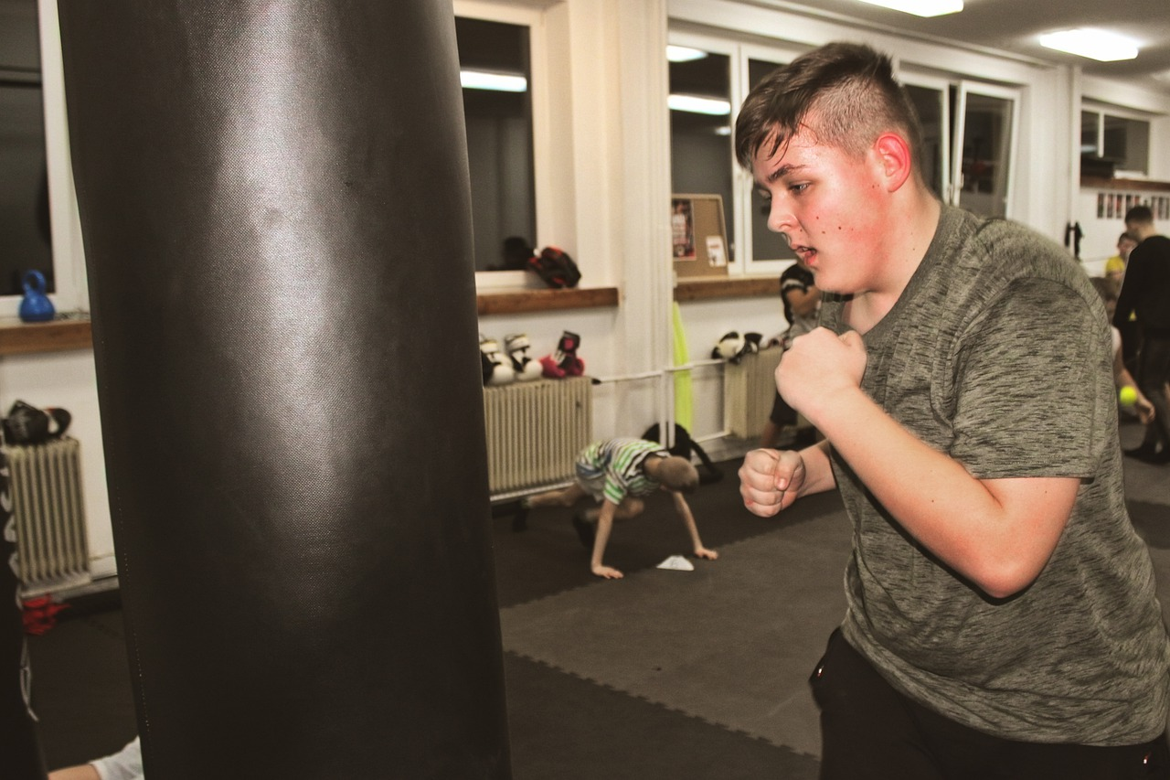 Teenage boy boxing on a punchbag