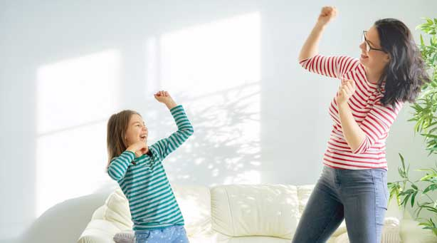 Mother and daughter dancing together at home