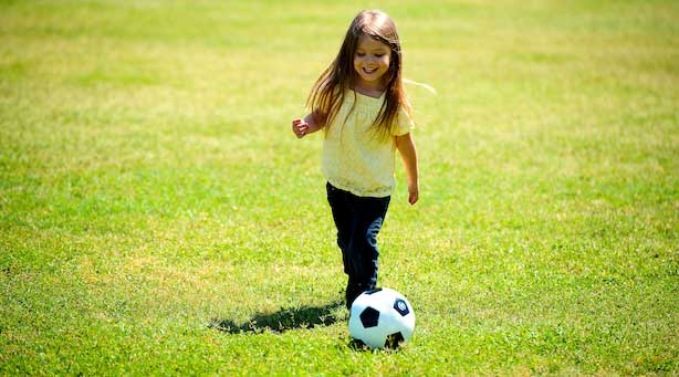 A young girl playing football on grass