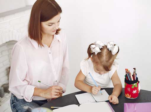 A woman homeschooling her young child