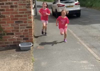 Two young girls running the Daily Mile at their home