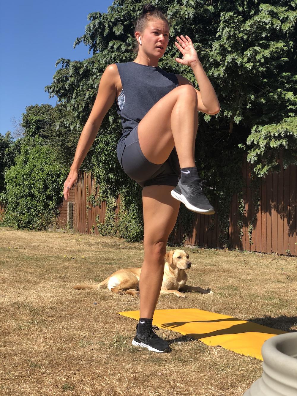Millie exercising on grass knee raise