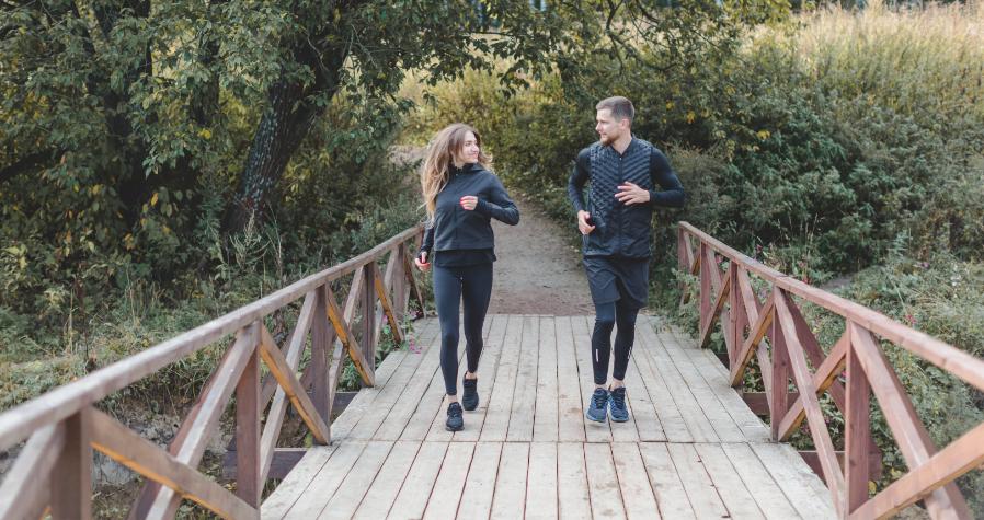 Young couple running on bridge