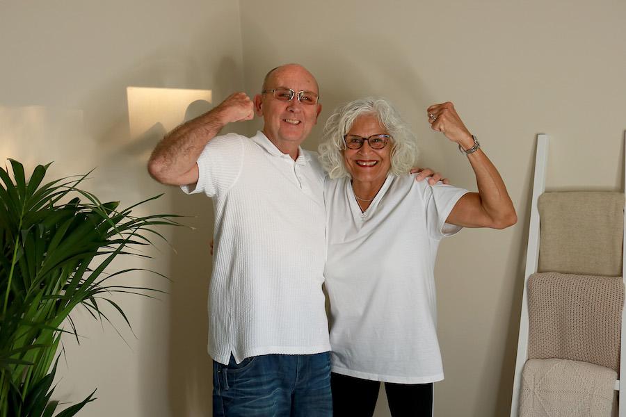 Carol and Colin Hammond posing with arms raised