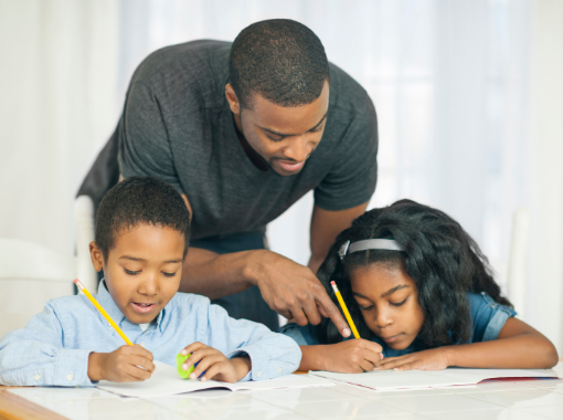 Dad helping two kids with school work